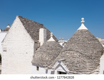 Alberobello, Italy - August around, 2016: Geometrically shaped roofs built of stone, characteristic of the ancient houses of Alberobello in Puglia, Italy.