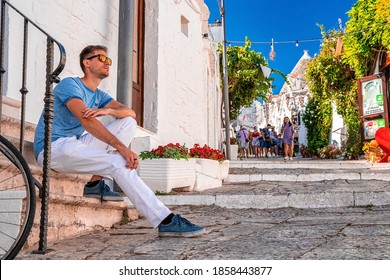 Alberobello, Italy. July 10, 2020. Young man sitting by the trulli houses in Alberobello, province Bari, region Puglia, Italy. Beautiful Italy, Bari region.