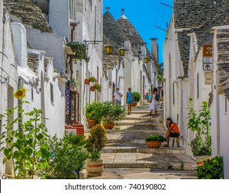 "ALBEROBELLO, ITALY - JULY 27, 2011 - Picturesque street in the old town with the traditional Apulian dry stone huts with a conical roof, known as ""trulli""."