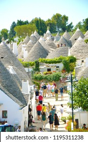 ALBEROBELLO, ITALY - JULY 31, 2017: Beautiful town of Alberobello with trulli houses among green plants and flowers, main touristic district, Apulia region, Southern Italy