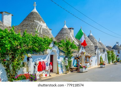 ALBEROBELLO, ITALY, JUNE 21, 2014: Tourists are enjoying sunny day among trulli houses in Alberobello, Italy.