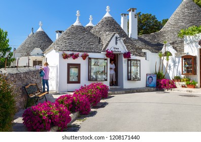 ALBEROBELLO, ITALY - JUNE 28, 2014: Alberobello's famous Trulli, the characteristic cone-roofed houses of the Itria Valley, Apulia, Southern Italy. Al Bano Wine Shop.
