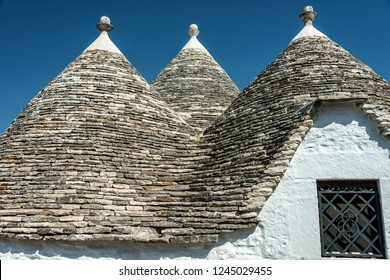 ALBEROBELLO, ITALY - JUNE 30, 2018: Alberobello's famous Trulli, the characteristic cone-roofed houses of the Itria Valley, Apulia, Southern Italy.