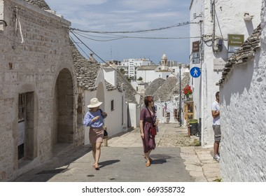 Alberobello, Italy - June 6, 2017: Tourists visit Alberobello, a small town and comune of the Metropolitan City of Bari. It has about 10,700 inhabitants and is famous for its unique trullo buildings.