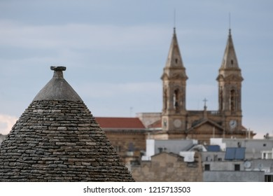 Alberobello Italy. September 2018. Conical roof of trulli house in Alberobello, Puglia, Italy, with the spires of Alberobello Cathedral in the background.