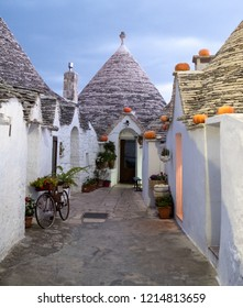 Alberobello, Italy. September 2018. Dry stone trulli houses on street in  Alberobello, Puglia. Pumpkins have been placed on the eaves to celebrate Halloween. Photographed at sunrise.