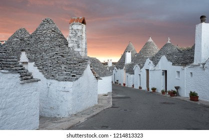 Alberobello Italy. September 2018. Traditional dry stone conical roofed trulli houses on a street in the Aia Piccola area of Alberobello, Puglia. Photographed early morning with red sky in background.