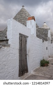 Alberobello, Italy. September 2018. . White-washed conical roofed trulli house behind a gate in the town of Alberobello in Puglia, Southern Italy.