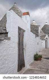 Alberobello, Italy. September 2018. . White-washed conical roofed trulli house behindwhite washed wall in the town of Alberobello in Puglia, Southern Italy.