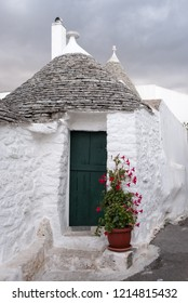 Alberobello, Italy. September 2018. . White-washed conical roofed trulli house with green door in the town of Alberobello in Puglia, Southern Italy.