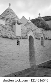 Alberobello, Italy. September 2018. White-washed conical roofed trulli house behind white washed wall in the town of Alberobello in Puglia, Southern Italy. Photographed in monochrome.