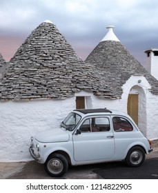 Alberobello, Italy. September 2018. White-washed trulli house with white Fiat vintage cinquecento 500 car parked in front, in the town of Alberobello in Puglia, Southern Italy.