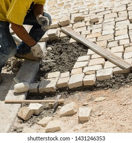 """Alberobello, Italy-June 20, 2019: Worker reconstructs the pedestrian street with the """"sanpietrini"""", the name of the stones used in antiquity for this type of pavement in the ancient villages."""