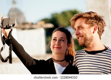 Alberobello, Puglia, Italy, October 2018: An attractive young couple take a selfie with their camera at Alberobello, a popular tourist destination in southern Italy.