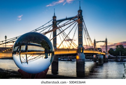 Albert Bridge in Chelsea, seen through a crystal ball at dusk, from the south bank of the river Thames.