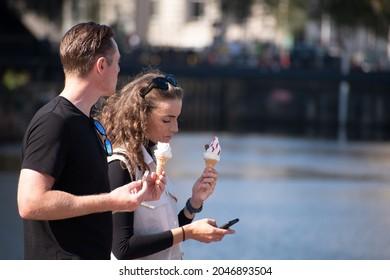 Albert Dock, Liverpool  September 16th 2021: Couple walking in the sunshine enjoying ice cream, woman on phone, Albert Dock