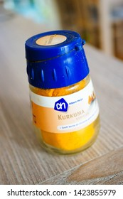 Albert Heijn kurkuma spice in a small plastic jar on a wooden table in soft focus on circa April 2015 in Poznan, Poland.