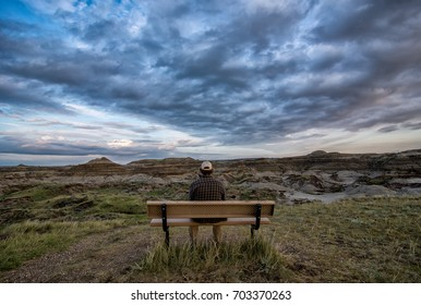 The Alberta badlands in dinosaur provincial park with man sitting on bench