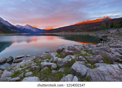 Alberta, BC Canada - July 9, 2018: A photographer taking picture of Beautiful sunset over Medicine Lake, Jasper National Park, Alberta, Canada. The Lake is located 20 km  southeast of Jasper.