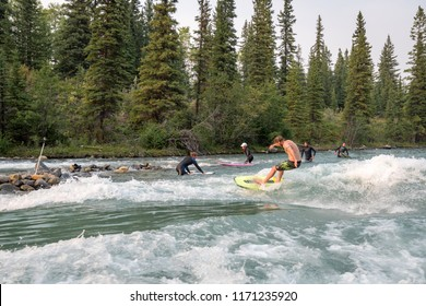 """Alberta, Canada, August 30, 2017 - River surfers surfing the man made """"Mountain Wave"""" on the glacier fed Kananaskis River in landlocked Alberta.  River surfing is fast becoming a popular new sport."""