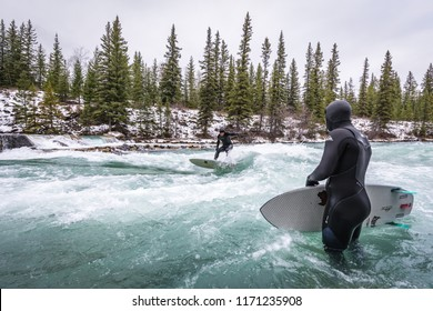 """Alberta, Canada, November 17, 2017 - River surfers surfing the man made """"Mountain Wave"""" on the glacier fed Kananaskis River in landlocked Alberta.  River surfing is fast becoming a popular new sport."""