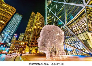 "Alberta, Canada, SEP 29, 2017 - Night view of the popular ""Wonderland"" sculpture by famous artist Jaume Plensa sits in-front of The Bow tower in Calgary, Alberta,Canada"