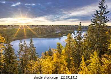 Alberta rural landscape with harvested field and north Saskatchewan river bank and island in the light of rising sun with sun rays