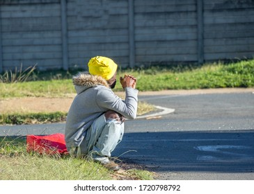 Alberton, South Africa - May 3, 2020: unidentified black man sits on a street corner during the covid-19 national lockdown hoping for a handout or a temporary job opportunity image in horizontal forma