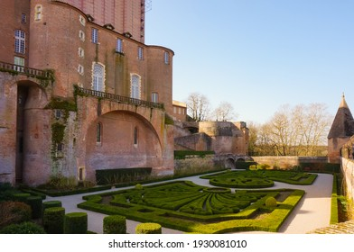 Albi, France - Feb. 2021 - Overhanging the French-style terraced garden, the main part of the Bishop's Palace of the Berbie, an imposing brick castle which is now home to the Toulouse-Lautrec Museum