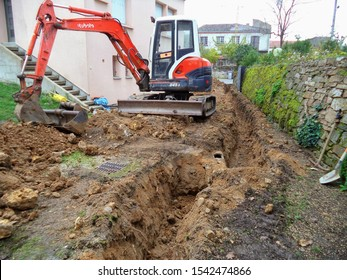 Albi, France - March 2016 - Tracked mini excavator from the Japanase manufacturer Kubota in a construction site, provided with several buckets, digging a trench in the ground