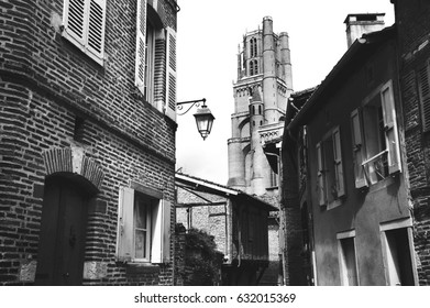 Albi (Roussillon-Languedoc, France). View of Cathedral Basilica of Saint Cecilia (UNESCO World Heritage Site) through a narrow medieval with lantern lamp. Black and white.