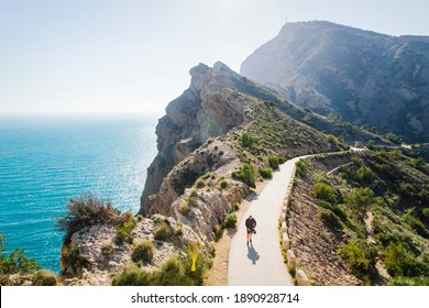 Albir, Costa Blanca, Spain - 10 February 2020: Tourist walking on scenic walking path along steep cliffs along the ocean in the natural park 'Serra Gelada' in Albir