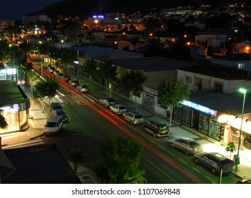 Albir, Spain - July 23 2012:   A night time view of Av De L'Albir with parked cars and traffic trails