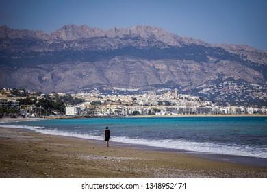 ALBIR, SPAIN - MARCH 25, 2019: Lonely woman on a beautiful beach of Albir