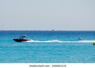Albir, Spain - September 11 2011:   A power boat and water skier in the sea off Albir Beach by Passeig De Les Estreles
