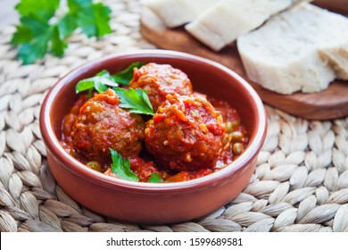 Albondigas - Spanish cuisine traditional homemade meatballs in rich tomato sauce served with fresh parsley and bread as a snack -  tapas in terracotta dish.