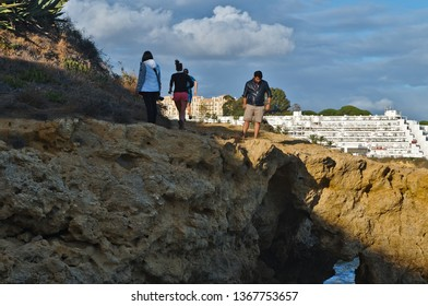 Albufeira, Algarve / Portugal - April 04 2019: People running and walking on the cliffs of Albufeira. Algarve, Portugal