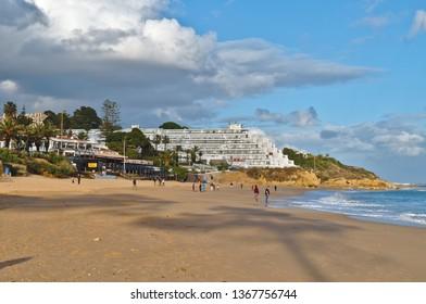 Albufeira, Algarve / Portugal - April 04 2019: Oura beach scene during afternoon. Popular summer travel destination