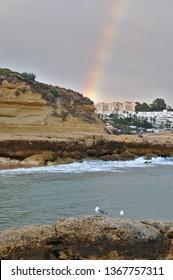 Albufeira, Algarve / Portugal - April 04 2019: Beautiful Rainbow sight in Aveiros beach. Albufeira