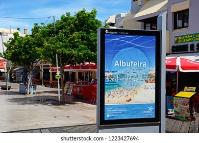 ALBUFEIRA, PORTUGAL - JUNE 10, 2017 - Pavement cafes in the main square in the old town during the morning with an advertising board in the foreground, Albufeira, Portugal, Europe, June 10, 2017.
