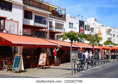 ALBUFEIRA, PORTUGAL - JUNE 10, 2017 - Pavement cafes along Av 25 de Abril in the old town with tourists passing by, Albufeira, Algarve, Portugal, Europe, June 10, 2017.