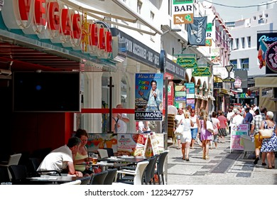 ALBUFEIRA, PORTUGAL - JUNE 10, 2017 - Tourists relaxing at a pavement cafe in the old town with shops and shoppers to the rear, Albufeira, Algarve, Portugal, Europe, June 10, 2017.