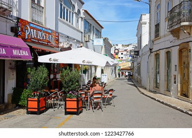 ALBUFEIRA, PORTUGAL - JUNE 10, 2017 - Tourists relaxing at a pavement cafe in the old town, Albufeira, Algarve, Portugal, Europe, June 10, 2017.