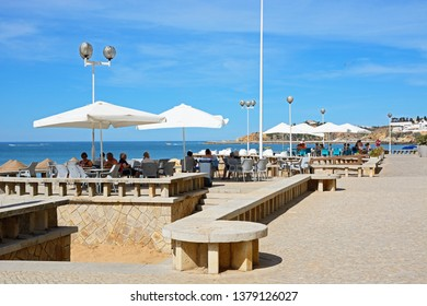 ALBUFEIRA, PORTUGAL - JUNE 10, 2017 - Tourists relaxing at a pavement cafe overlooking the sea, Albufeira, Portugal, Europe, June 10, 2017.