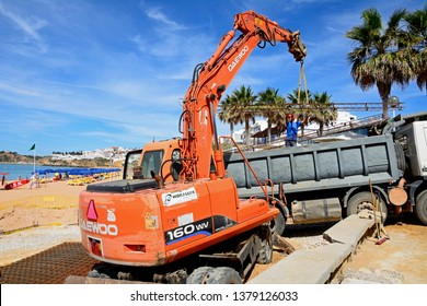 ALBUFEIRA, PORTUGAL - JUNE 10, 2017 - Construction worker on the beach moving girders with an excavator, Albufeira, Portugal, Europe, June 10, 2017.