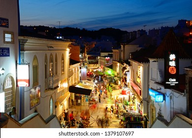 ALBUFEIRA, PORTUGAL - JUNE 12, 2017 - Elevated view of the R 5 de Outubro shopping street in the evening with tourists enjoying the setting, Albufeira, Portugal, Europe, June 12, 2017.