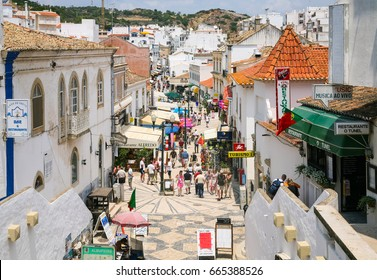 ALBUFEIRA, PORTUGAL - JUNE 17, 2006: tourists on pedestrian shopping and restaurant street Rua 5 de Outubro in old town of seaside resort Albufeira in Algarve region of Portugal