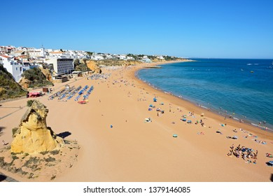 ALBUFEIRA, PORTUGAL - JUNE 6, 2017 -  Elevated view of the beach with tourists enjoying the setting and town buildings to the rear, Albufeira, Algarve, Portugal, Europe, June 6, 2017.