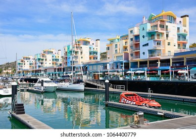 ALBUFEIRA, PORTUGAL - JUNE 8, 2017 - Yachts moored in the marina with apartments and waterfront businesses to the rear, Albufeira, Algarve, Portugal, Europe, June 8, 2017.