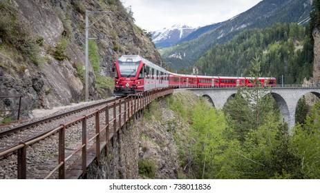 Albula - Switzerland - May 2017: Glacier train on famous landwasser Viaduct bridge.The Rhaetian Railway section from the Albula - Bernina area, Switzerland, Europe.